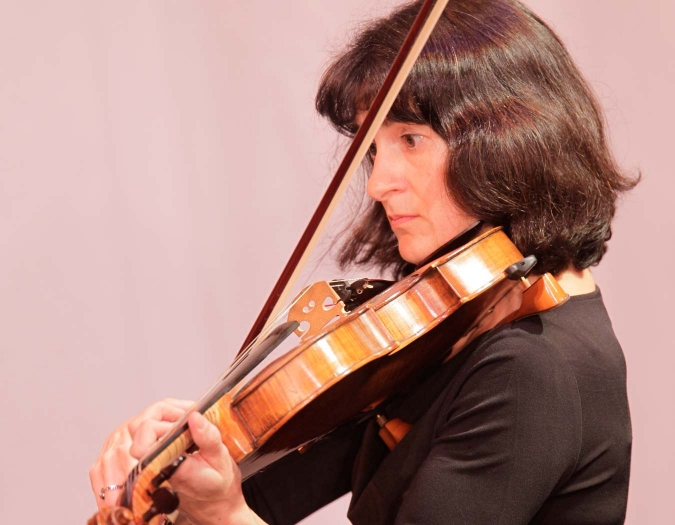 Image of Suzannah Chalik of the Naples Philharmonic on stage playing viola during a performance