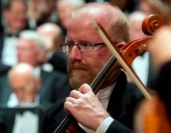 Image of Thomas May of the Naples Philharmonic on stage playing violin during a performance