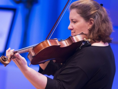 Image of Lisa Mattson of the Naples Philharmonic on stage playing a viola during a performance