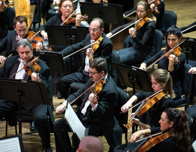 Image of members of the Naples Philharmonic on stage during a performance of classical music