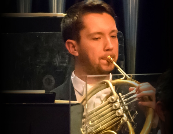 Image of Ryan Little of the Naples Philharmonic on stage playing horn during a performance