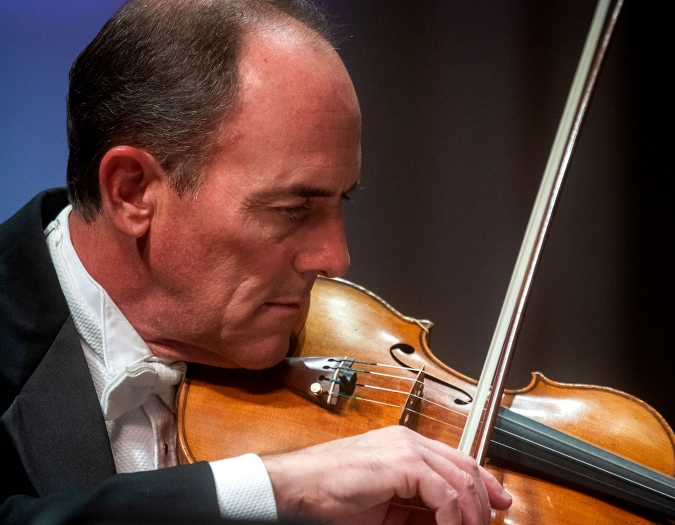 Image of Gregg Anderson of the Naples Philharmonic on stage playing violin during a performance
