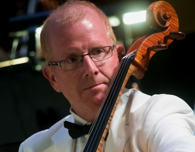Image of Thomas May of the Naples Philharmonic on stage playing a cello during a pops performance
