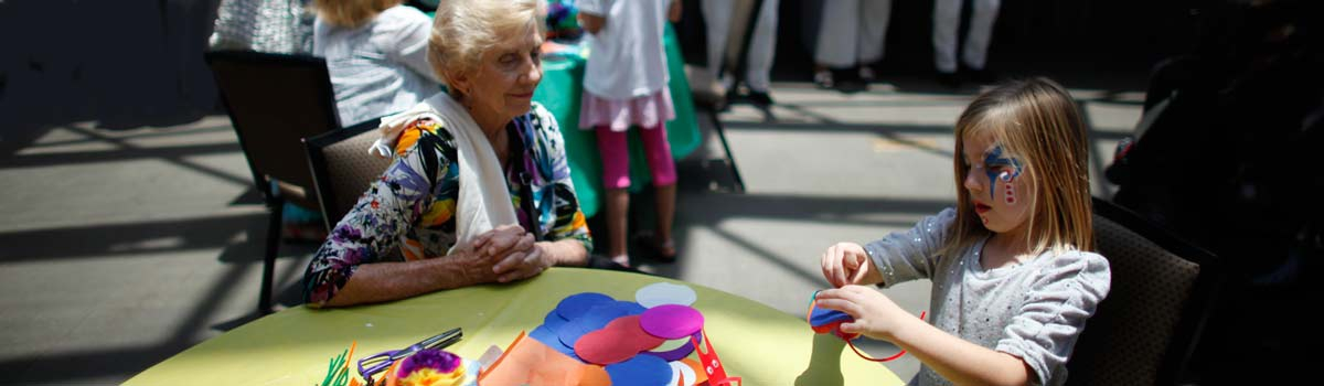 Image of a grandmother and her granddaughter sharing a moment of art-making on the Artis—Naples campus