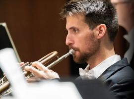 Image of Ansell Norris of the Naples Philharmonic on stage playing trumpet during a performance