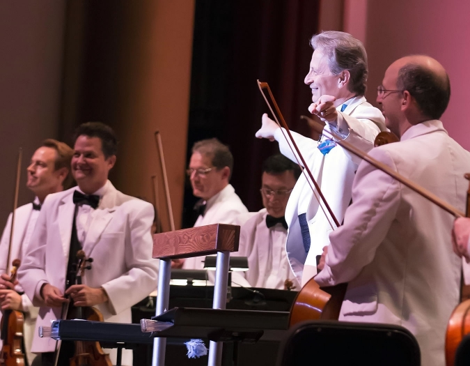 Image of Jack Everly, principal pops conductor of the Naples Philharmonic with members of the Naples Philharmonic on stage during performance