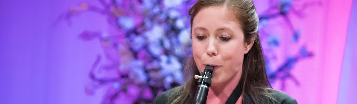 Image of Ashley R. Leigh of the Naples Philharmonic on stage playing clarinet during a performance