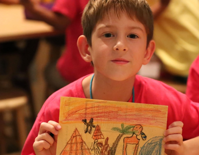 Image of young boy holding up his art during a Make and Take event