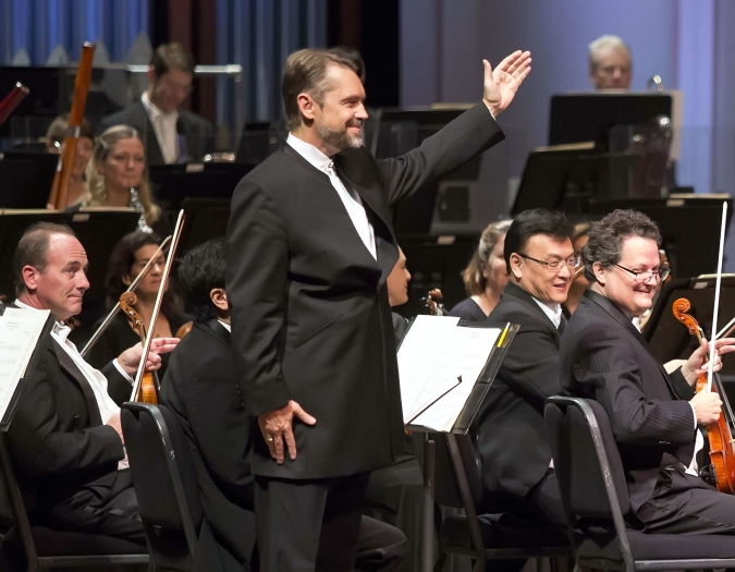 Image of Andrey Boreyko, conductor of the Naples Philharmonic on stage during a performance, with members of the Naples Philharmonic behind him