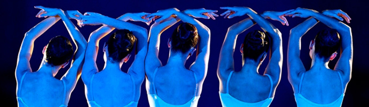 Image of ballet dancers in a line cast by blue light
