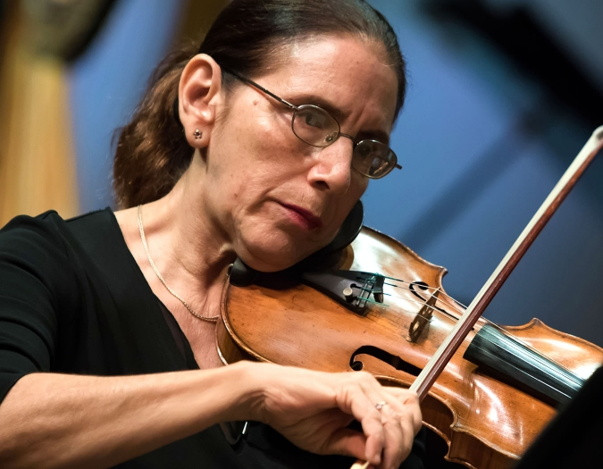 Image of Rebecca Ziv of the Naples Philharmonic on stage playing a violin during a performance