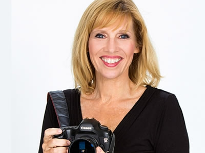 Image of artist Peggy Farren posing with a camera