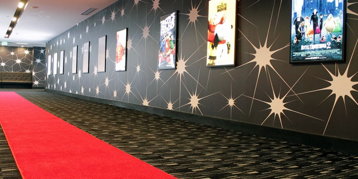 Image of the red carpet leading down the corridor of theaters at the Silverspot Theater venue where the films of the Naples International Film Festival take place