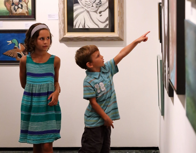 Image of young museum patrons viewing pieces of art at The Baker Museum during an Art After Hours event