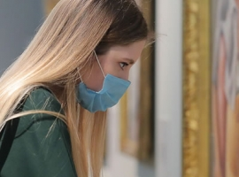 Image of a patron viewing a museum exhibition while wearing a face mask