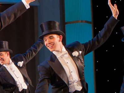 Image of a chorus-line of dancers in tuxedos on stage during a performance