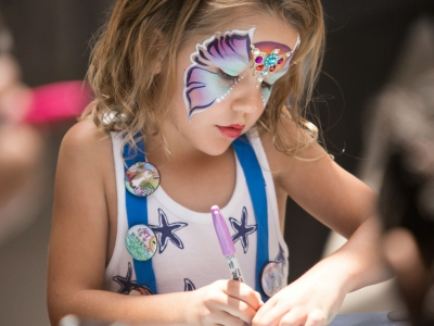 Image of child with face painting drawing at an art display