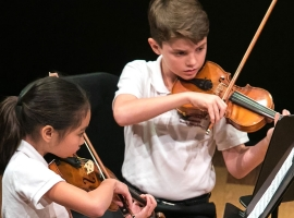 Image of student musicians performing on stage in a concert of the Naples Philharmonic Youth Symphonia