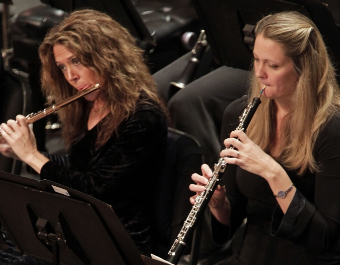 Image of Suzanne Kirton and Judy Christy of the Naples Philharmonic on stage playing wind instruments during a performance
