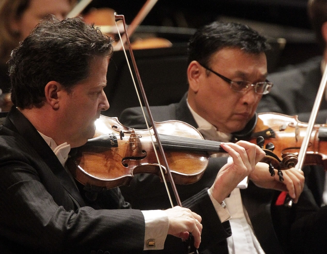 Image of Glenn Basham, concertmaster, and Ming Gao of the Naples Philharmonic on stage playing violins during a performance