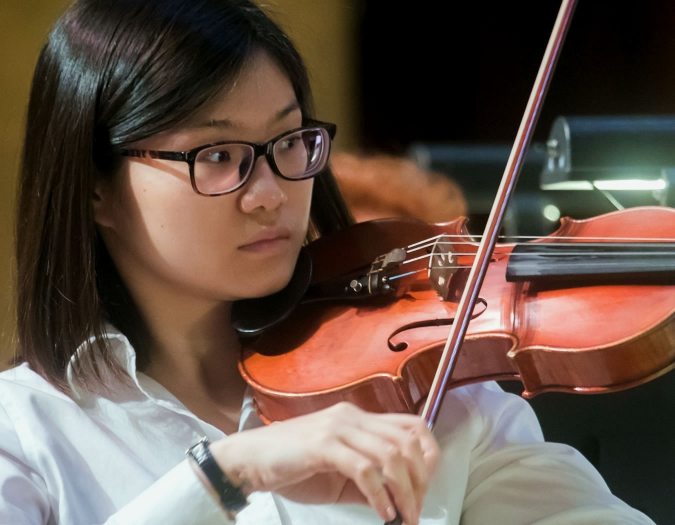 Image of Huiying Ma of the Naples Philharmonic on stage playing a violin during a performance