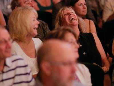 Image of audience members applauding and laughing during a performance in Hayes Hall at Artis—Naples