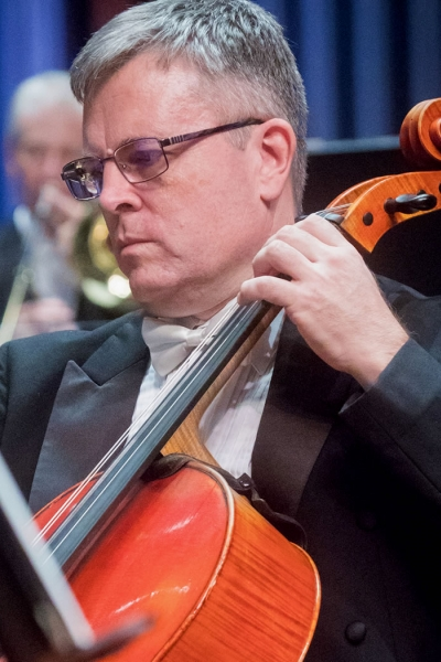 Image of John Marcy of the Naples Philharmonic on stage playing violin during a performance