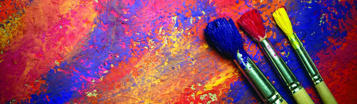 Image of paint brushes on a canvas of freshly painted colors representing the Artist Studio Tour at Artis—Naples