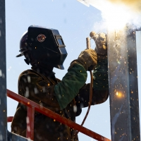 A worker welds the steel of the museum's frame.