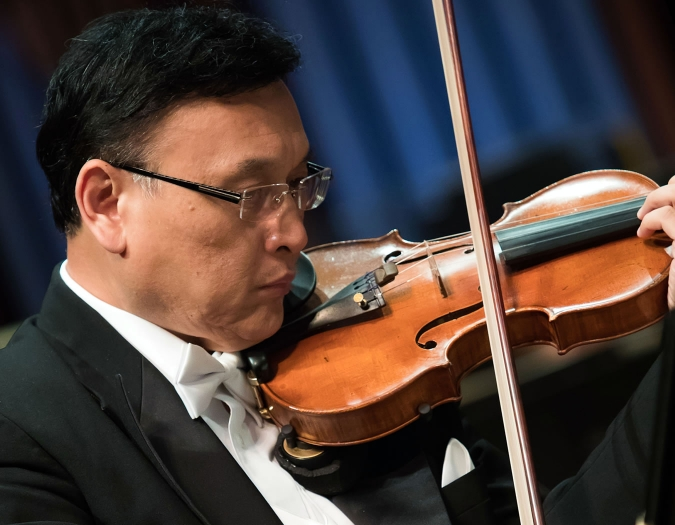 Image of Ming Gao of the Naples Philharmonic on stage playing violin during a performance