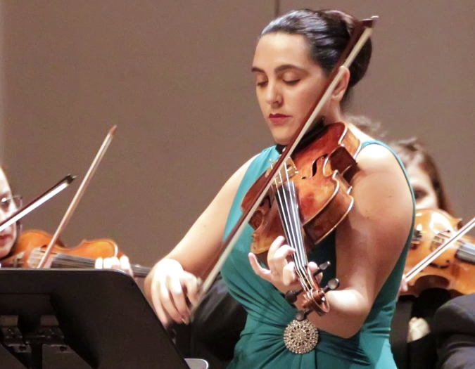 Image of Jessie Goegel of the Naples Philharmonic on stage playing viola during a performance