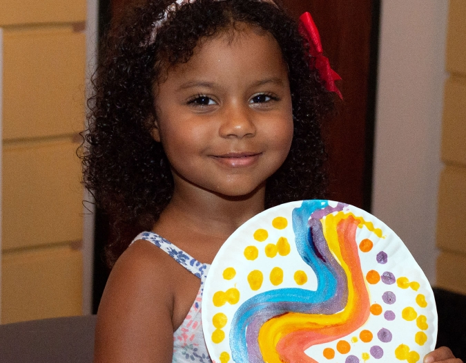 Image of a child showing off art that she made during a Community Day event