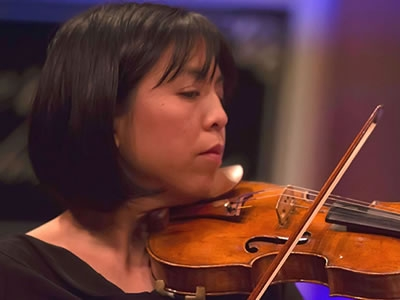 Image of Marlena Chow Morgan of the Naples Philharmonic on stage playing violin during a performance