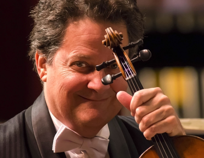 Image of Glenn Basham, concertmaster of the Naples Philharmonic posing with his violin