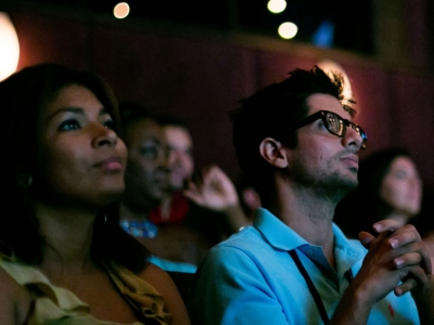 Image of patrons in a movie theater looking at the big screen during the Naples Internal Film Festival 2018 Films