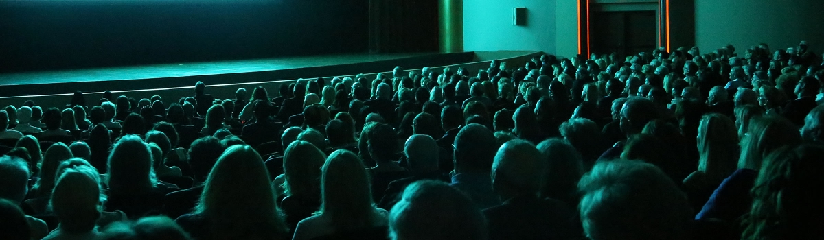 Image of a darkened theater with the glow of the movie screen reflecting off the audience watching the movie