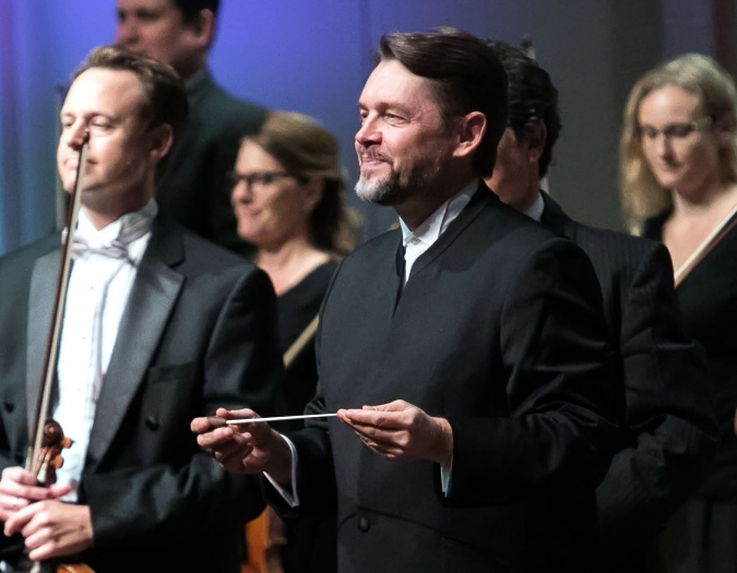 Image of Andrey Boreyko, conductor of the Naples Philharmonic on stage during a performance with musicians of the Naples Philharmonic