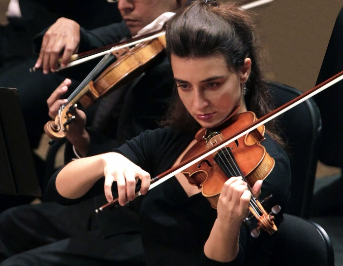 Image of Daniela Shtereva of the Naples Philharmonic on stage playing a violin during a performance