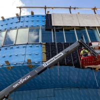 Workers secure limestone plates around the windows of the new breakout gallery.
