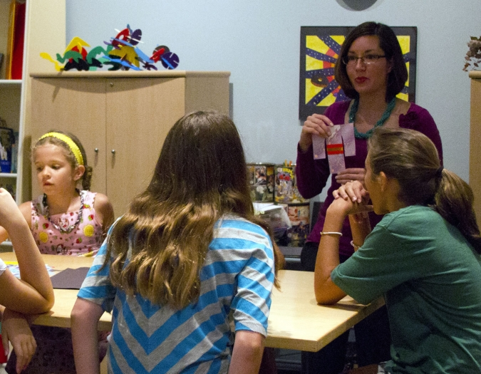 Image of children at a table of art supplies receiving instruction from an art teacher at a Make and Take event