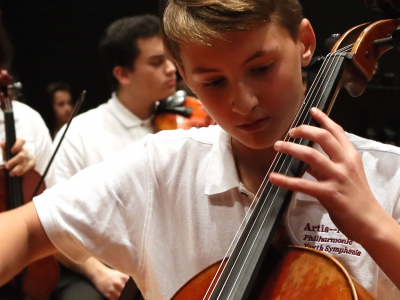 Image of a student musician performing on stage in a concert of the Naples Philharmonic Youth Symphonia