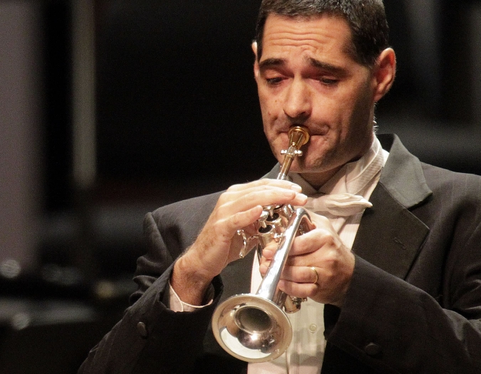 Image of Matthew Sonneborn of the Naples Philharmonic on stage playing trumpet during a classical music performance