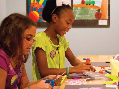 Image of young girls making art during a Make and Take event