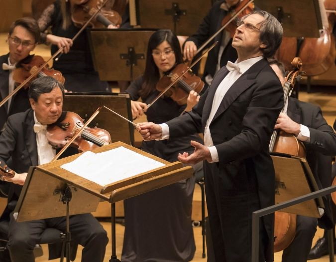 Image of Ricardo Muti, conductor of the Chicago Symphony Orchestra, with members of Chicago Symphony Orchestra on stage during performance