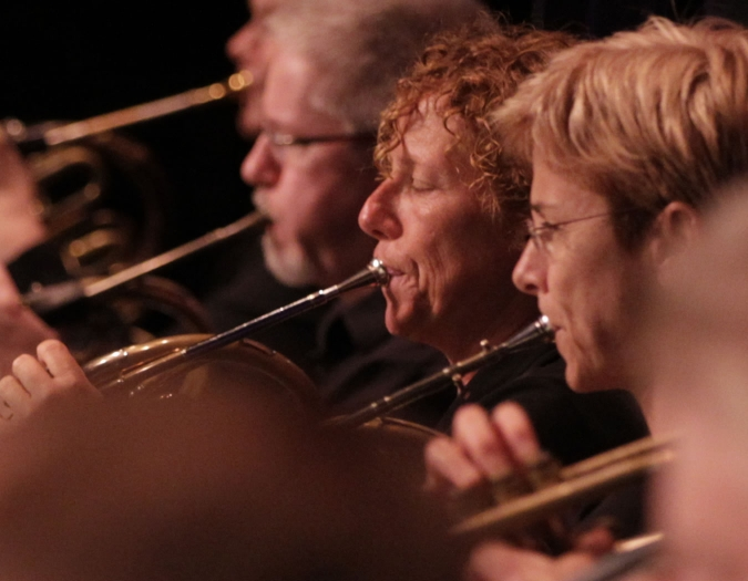 Image of Ellen Tomasiewicz and Tracy Leonard of the Naples Philharmonic on stage playing brass during a performance