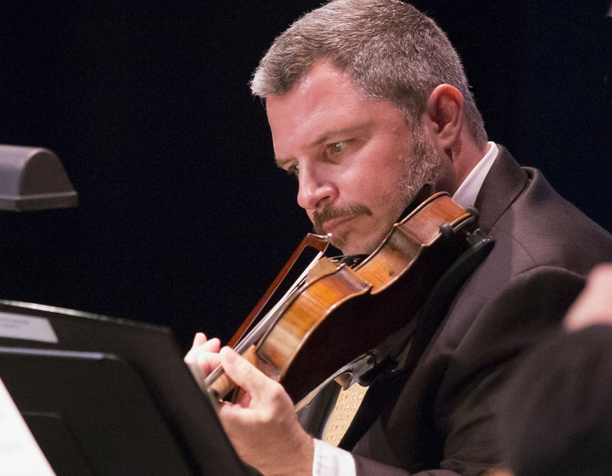 Image of David Mastrangelo of the Naples Philharmonic on stage playing a violin during a performance