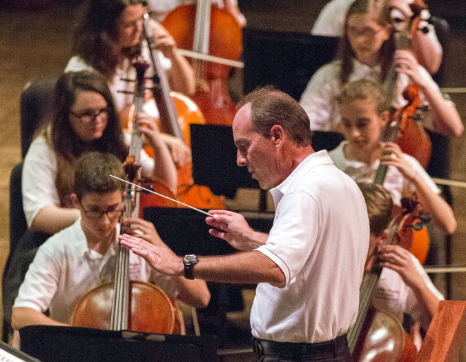 Image of student musicians performing on stage with Gregg Anderson conducting a concert of the Naples Philharmonic Youth Symphonia