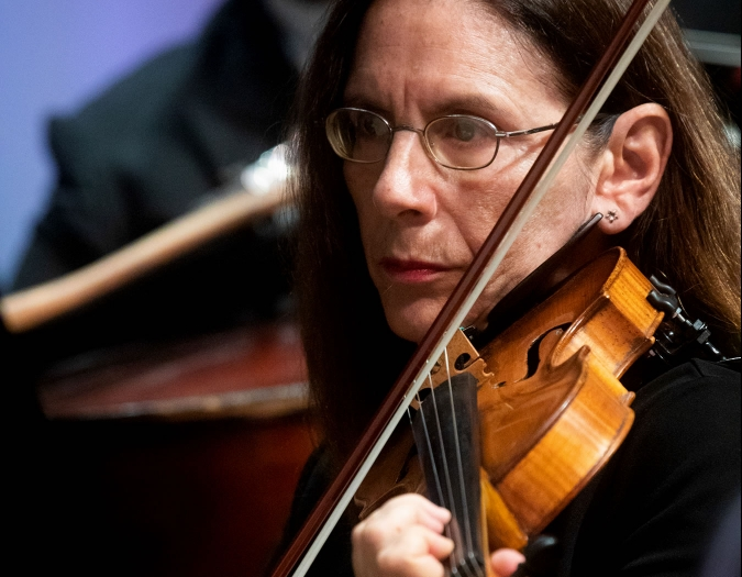 Image of Rebecca Ziv of the Naples Philharmonic on stage playing violin during a performance