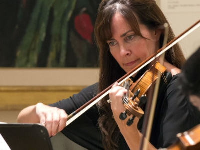 Image of Ruth Leone of the Naples Philharmonic on stage playing violin during a performance