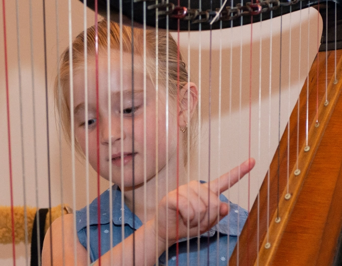 Image of a child playing a harp during a Community Day event